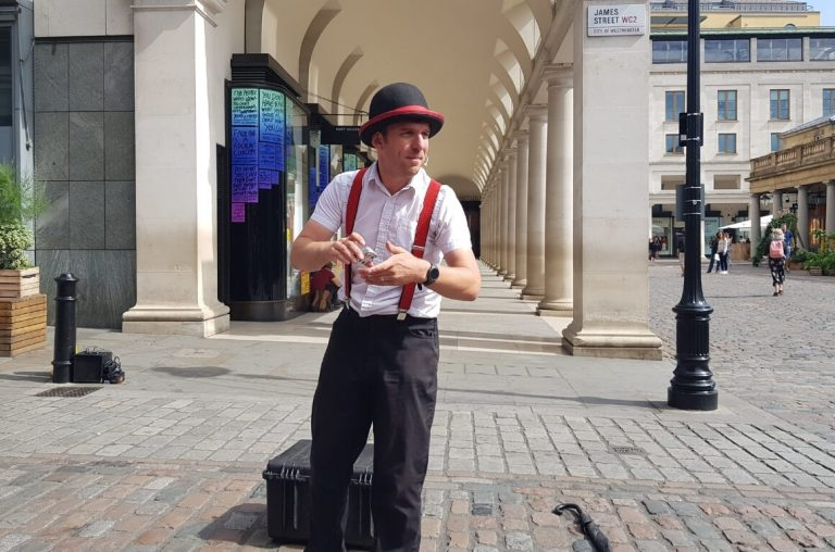 A Covent Garden busker with a deck of cards and bowler hat preparing for his performance.
