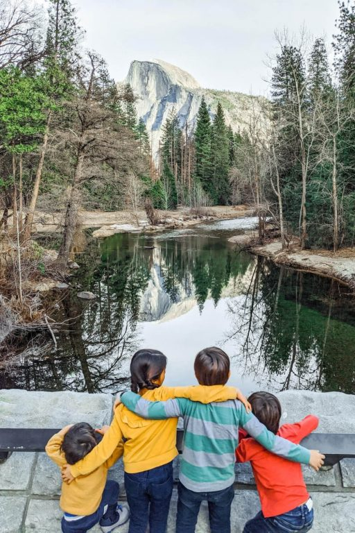 A group of four kids in front of a still lake surrounded by trees in Yosemite National Park