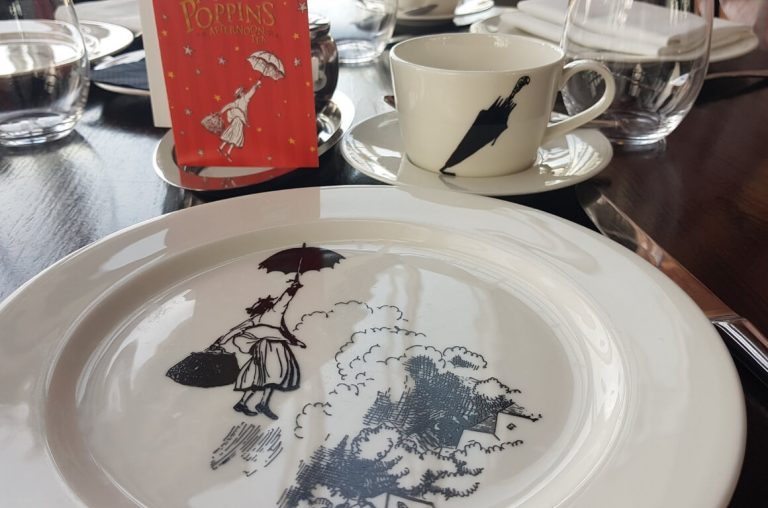 A picture of plates and cups themed with Mary Poppins pictures set out for afternoon tea on a table.