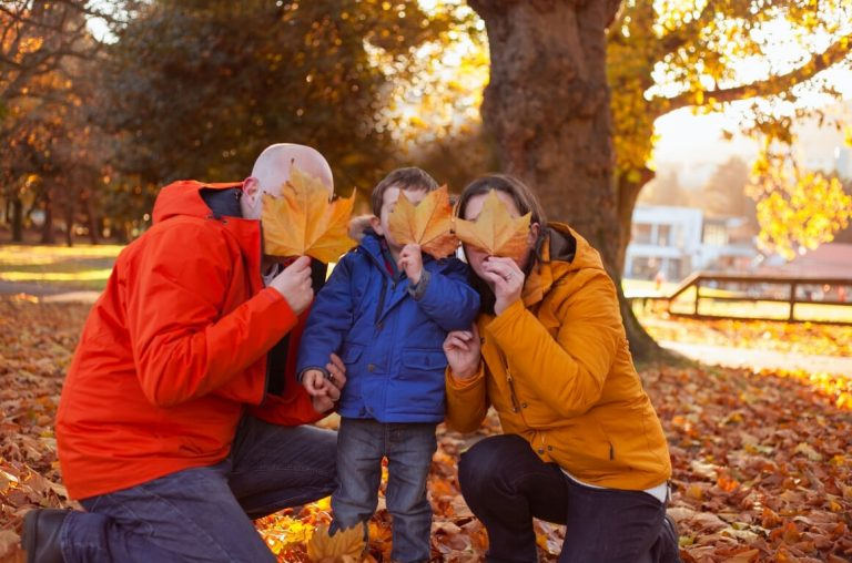 a picture of a family of three in bright jackets holding autumn leaves in front of their faces