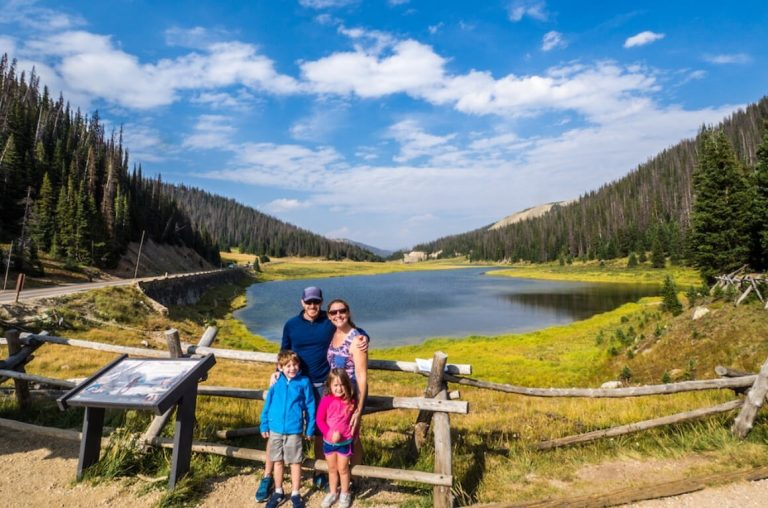 A family of four smiling in front of a lake surrounded by tall trees in the Rocky Mountain National Park