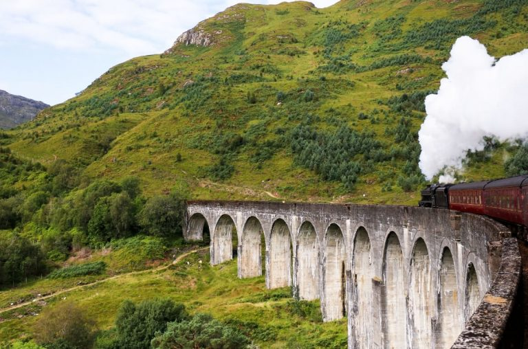 A picture of a steam train travelling along an aqueduct