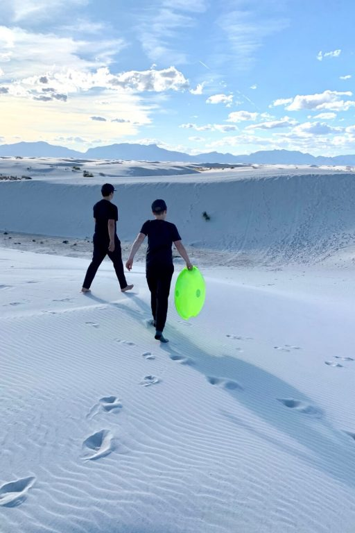 A picture of two kids walking towards a dune in the White Sands National Park