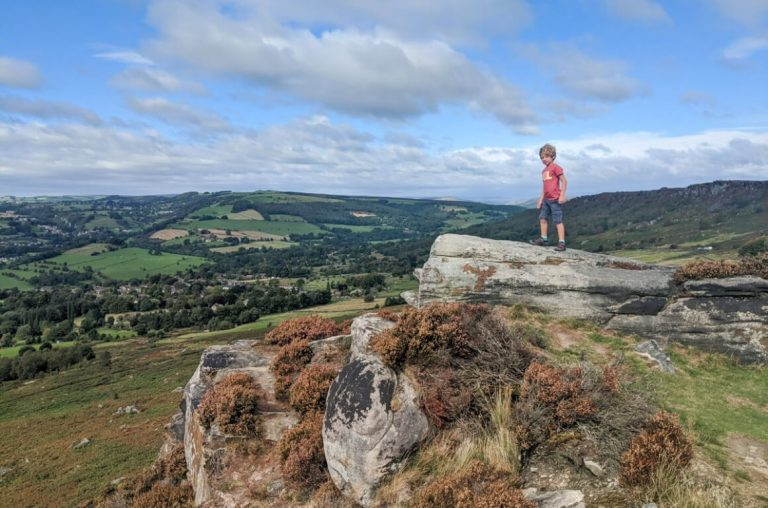 A picture of a young boy standing on a rocky outcrop at Baslow Edge in the Peak District