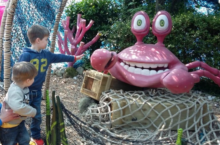 A picture of two young kids looking at a pink crab model at Blackgang Chine