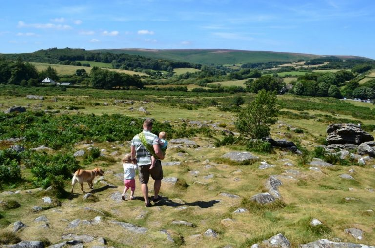 A picture of a dad with two kids taking a walk along a stony ground in the Dartmoor National Park