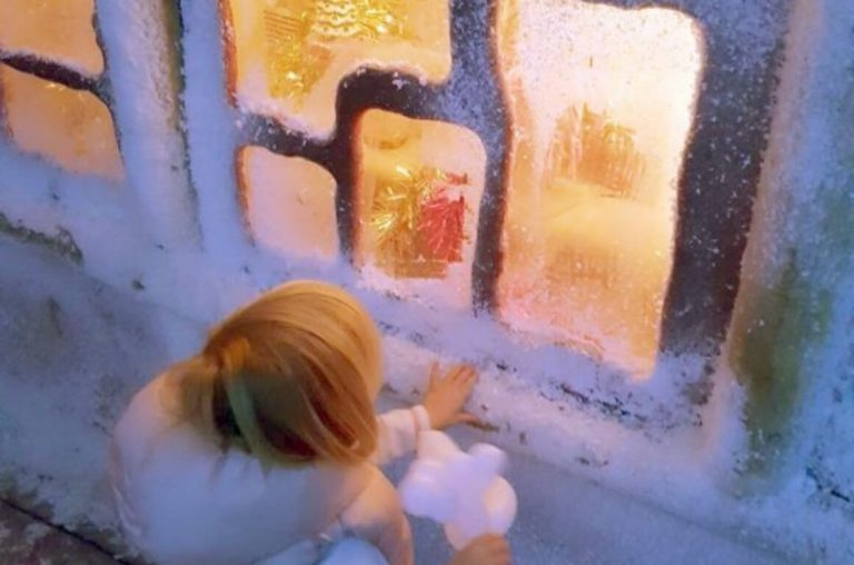 A little girl peeking through a frosted window of an ice house at the Marsh Farm Christmas Experience