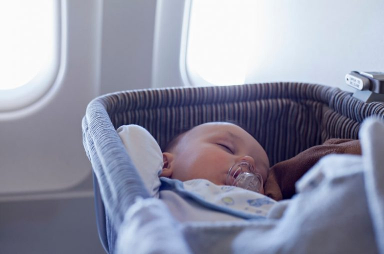 A baby asleep in an airplane bassinet