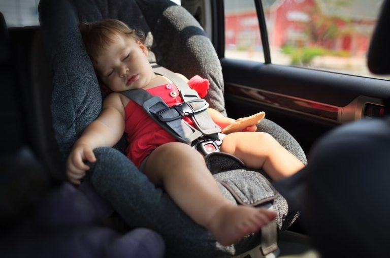 A picture of a baby asleep in a car seat