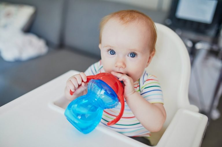 A picture of a baby in a high chair with a blue sippy cup