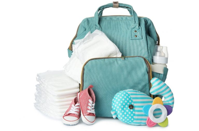 A picture of a green backpack diaper bag with a baby toy, diapers, bottle and pink baby shoes