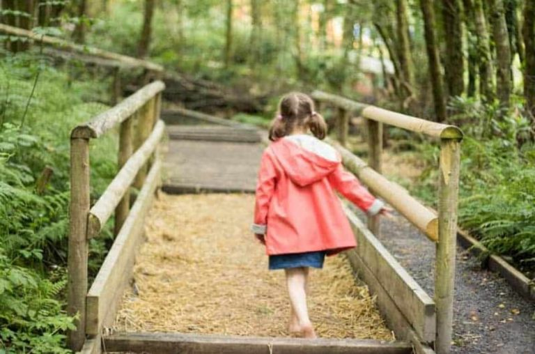 A picture of a girl in a pink coat walking in the forest at Greenwood Forest Park
