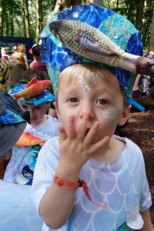 A picture of a boy with glitter on his face and a blue hat at the Just So Festival