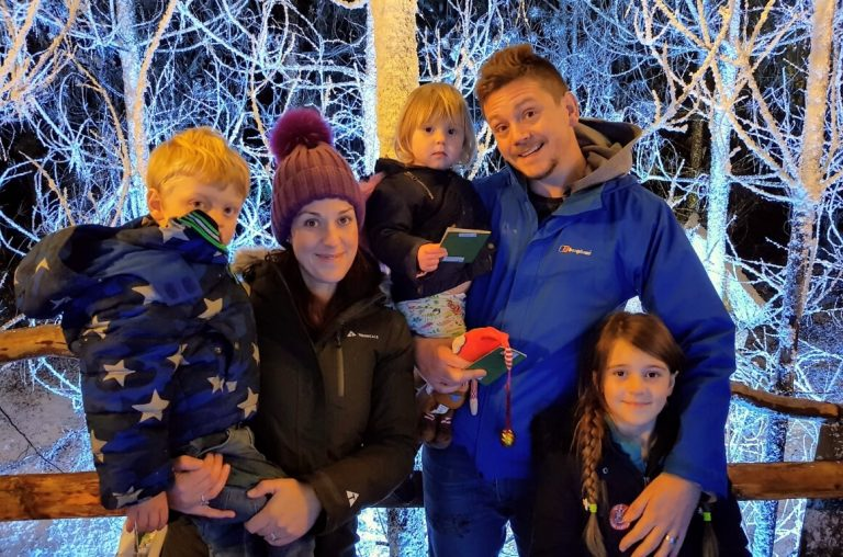 A picture of a family of five smiling in the winter wonderland of LaplandUK