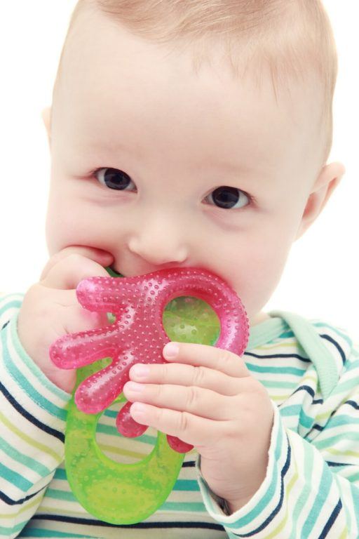 A picture of a baby with a pink and green teething toy in their mouth