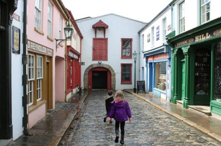 A picture of two young children walking through one of the streets at the living museum of the Ulster American Folk Park
