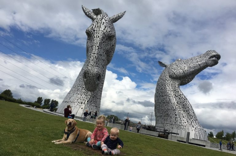 A picture of two kids and a dog sitting in front of the two Kelpies horse sculptures