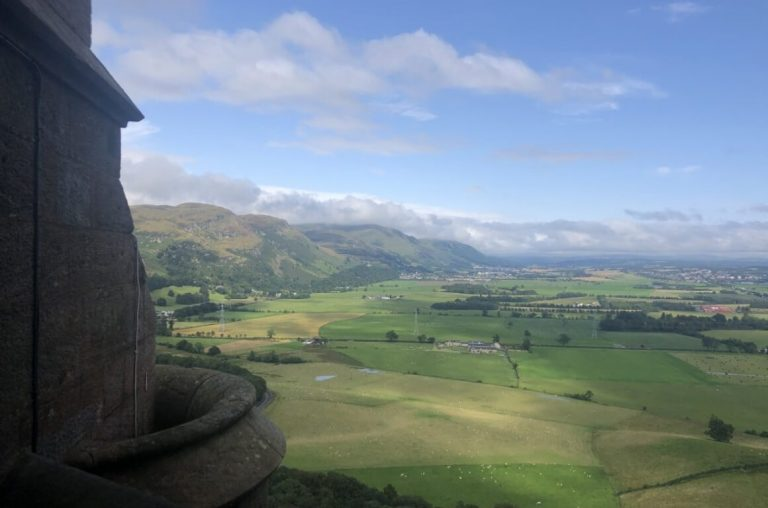 A view from the Wallace Monument of green fields under a blue sky