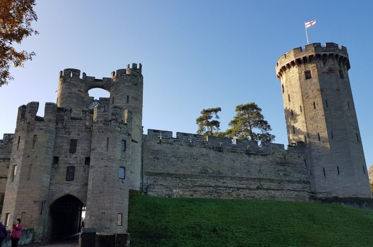 A picture of a tower and walls of Warwick Castle under a blue sky