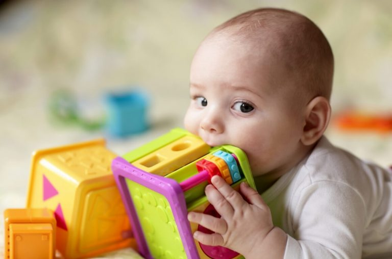 A picture of a baby playing with toys with the edge of one in their mouth