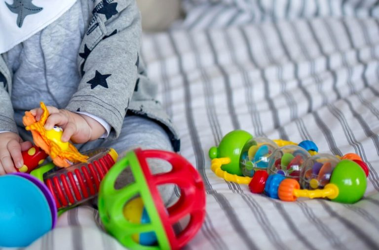 A picture of a baby's hands playing with brightly coloured toys